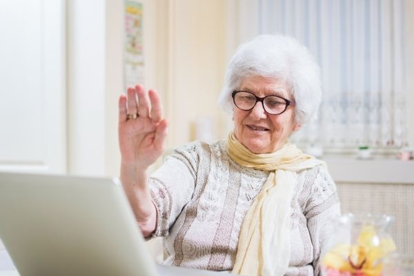 Fosters offer Zoom call service - an older grey haired lady sits in front of her laptop on a zoom call. She raises her hand to wave at the person on screen and has dark framed glasses