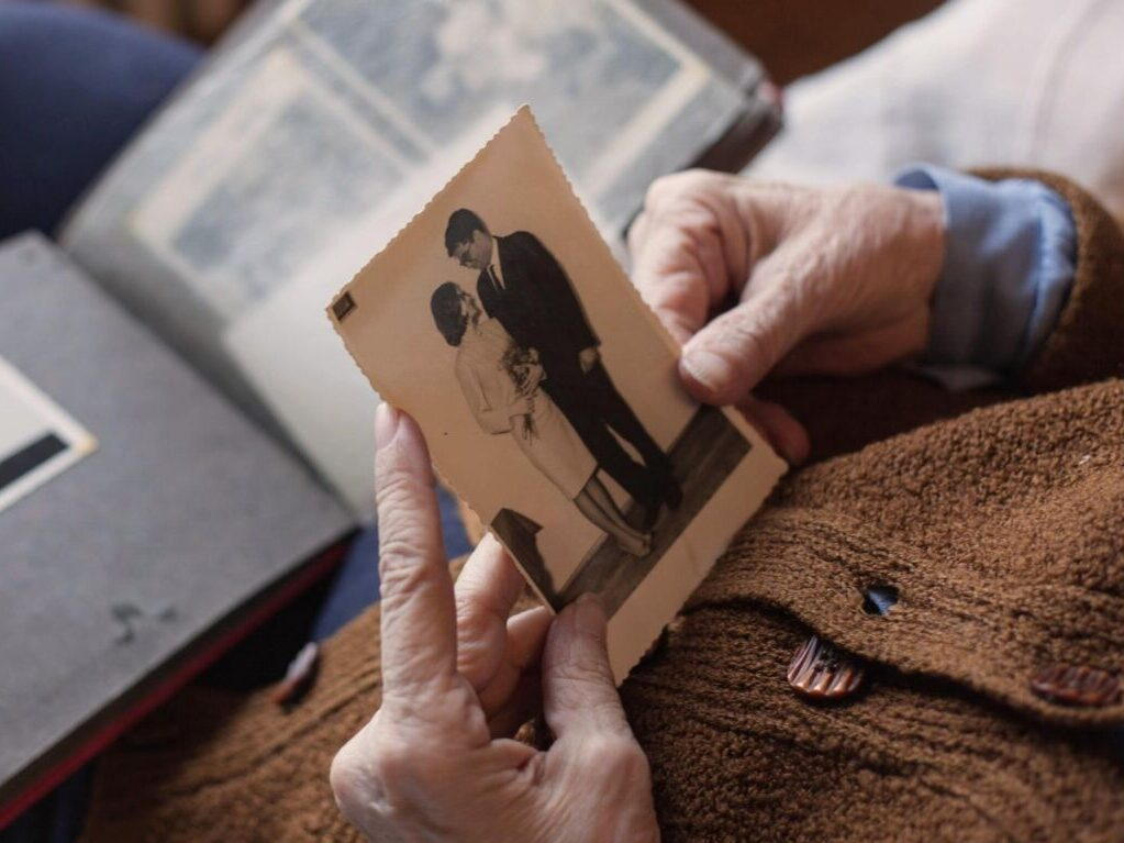 How to write the perfect eulogy - an elderly person holds a photograph, with an album resting on their knees