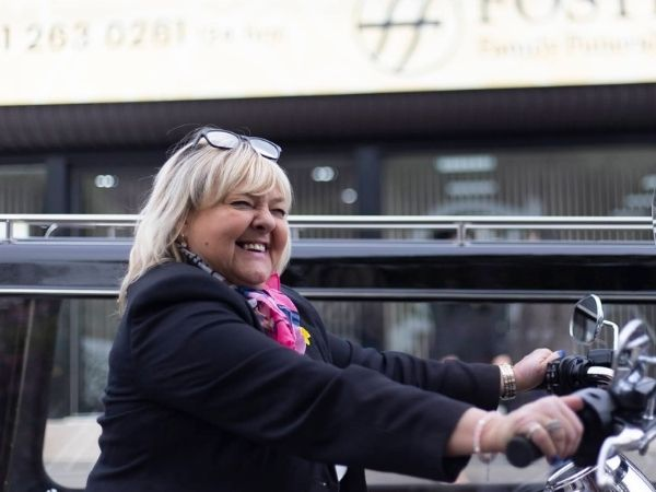 Edinburgh Funeral Arranger Elaine Carr smiles broadly as she sits on a motorbike with Fosters funeral parlour in the background
