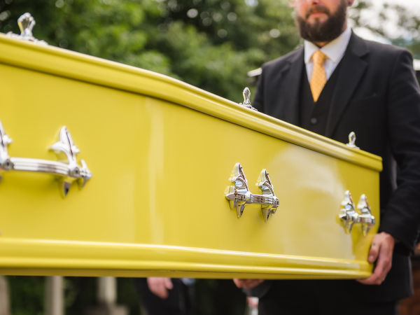 Bright coloured coffin at modern funeral