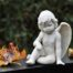 Direct Cremation Fosters - a white cherub sits on a black marble slab with some autumn leaves scattered around