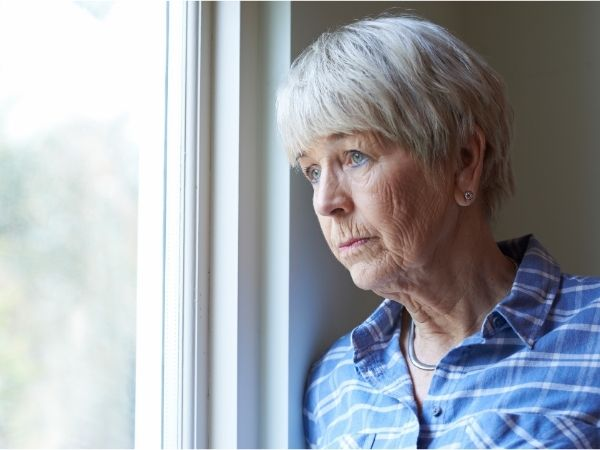 National Day of Reflection - a mature woman with short grey hair wearing a blue shirt looks out a window
