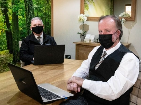 Two male staff members wearing smart suits sit at a table in front of laptops, Both wear face masks