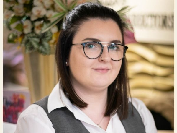 Fosters Hamilton - funeral arranger Sarah has shoulder length dark hair, blue rimmed glasses and a smart outfit