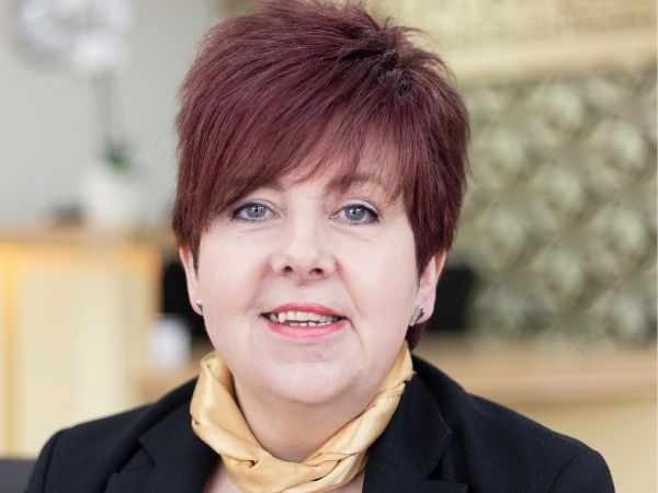 Fosters Ayr - Sharon wears a yellow scarf and dark suit, her hair is short
