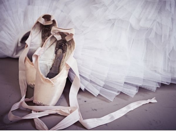 a pair of pink worn ballet shoes with long ribbons rest against a wooden floor and a white tulle skirt
