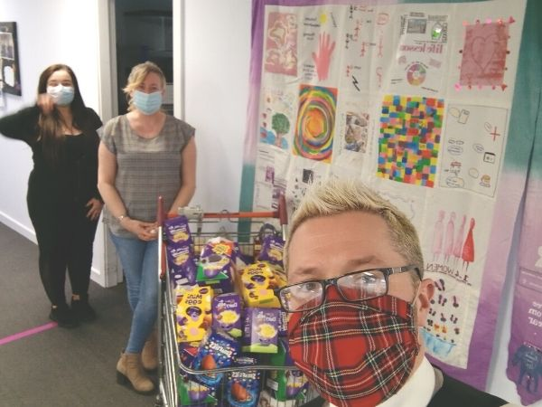 Chris with Women's Aid South Lanarkshire and a trolley full of Easter Eggs