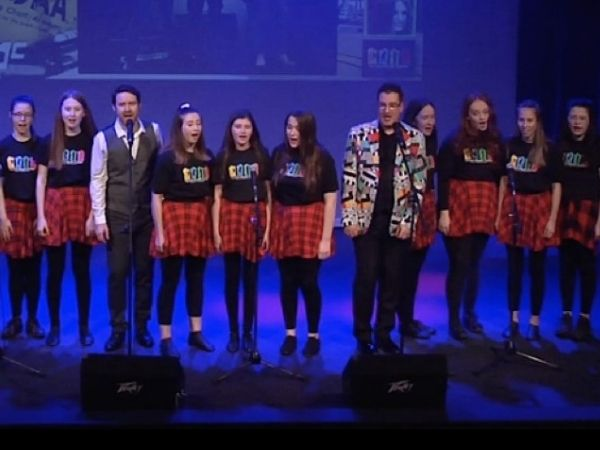 A group of girls wearing red tartan skirts and black tops sing on a stage accompanied by two male singers