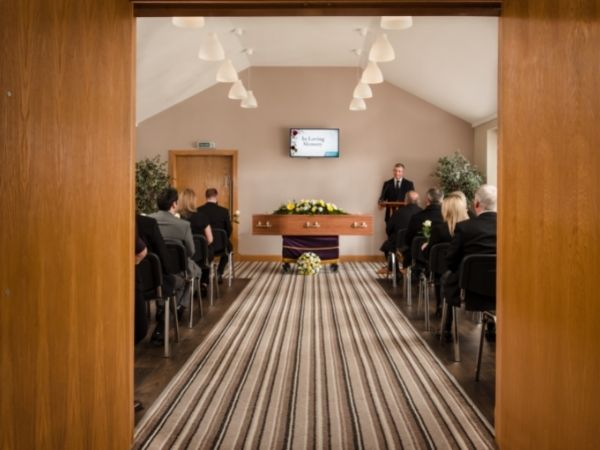 Fosters funeral home in Scotland, a bright and modern, comfortable space with mourners and a coffin