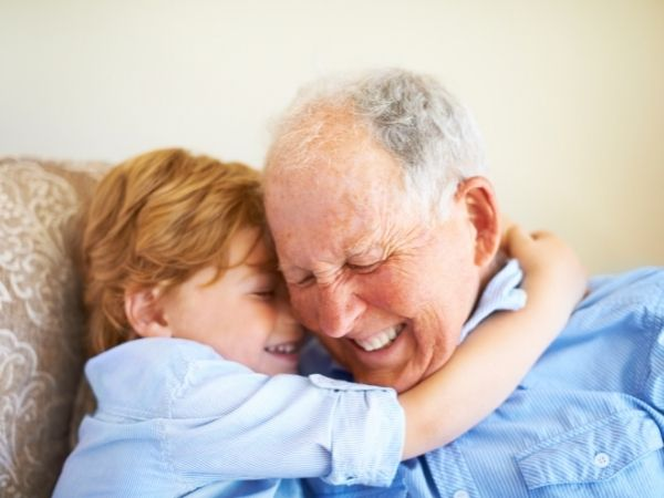 A redhaired boy wraps his arms around his Grandad's neck.
