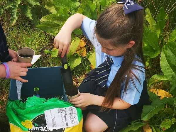 Fosters Rutherglen -a 7 year old girl wearing school uniform fills a plantpot with earth and seeds