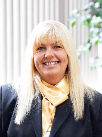 Funeral arranger Julie has long blonde hair, a gold necktie and a black jacket