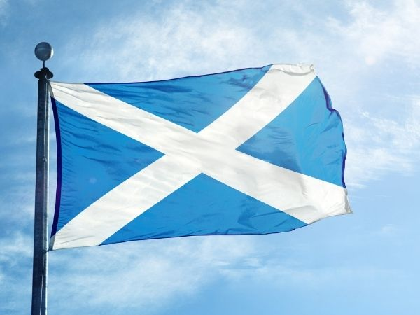 Scotland flag blowing in the breeze on a flag pole with blue skies