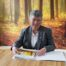 Debra has short grey hair and wears a smart shirt and jacket. She is seated at a table with a woodland wallpaper behind her