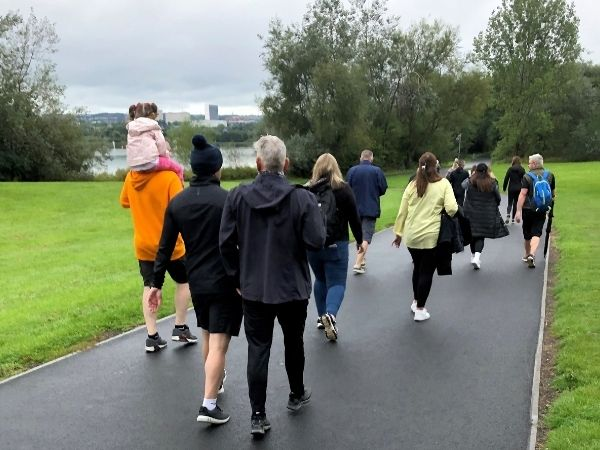 A group of people walk along a path at Strathclyde Park