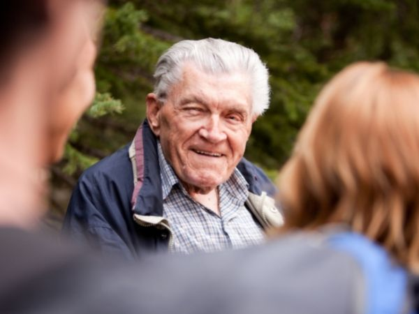 An older gentleman with grey hair smiles as a couple walk towards him, the couple are only seen from behind.