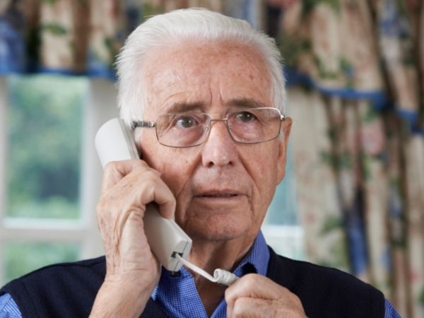 A grey haired man in glasses holds a telephone to his ear and listens intently, behind him are flowery curtains and he wears a blue shirt and jumper